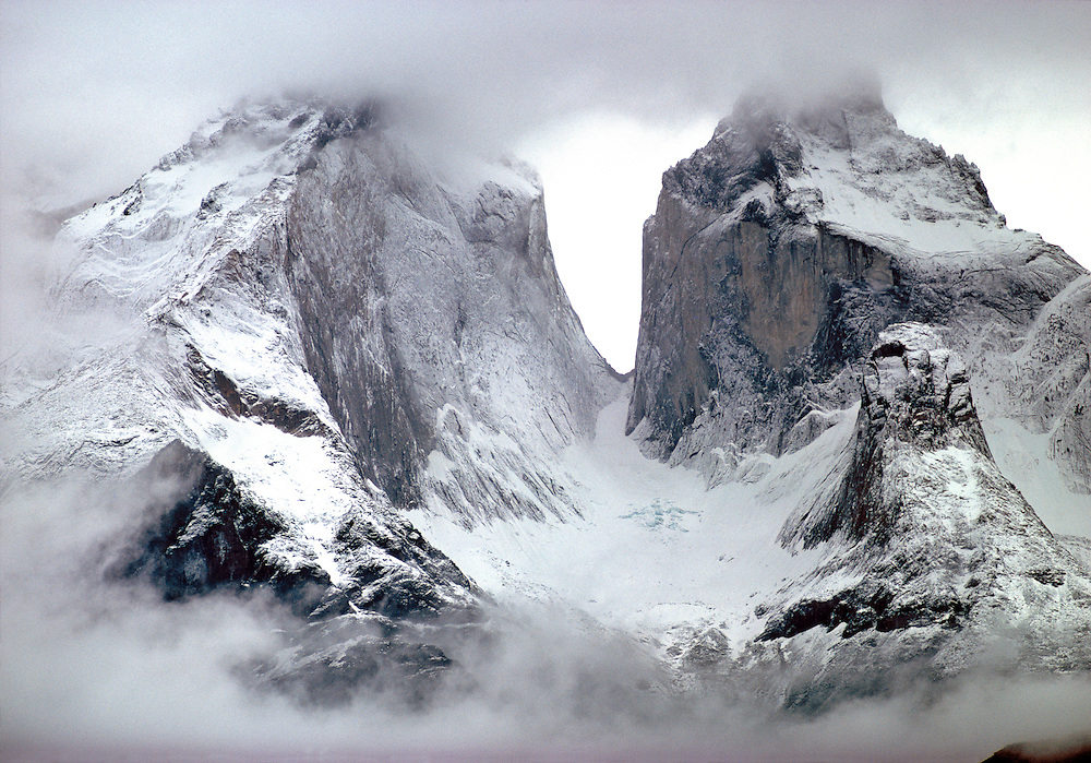 Fresh snow dusts the craggy, blue-hued Torres del Paine, Paine National Park, Chile.