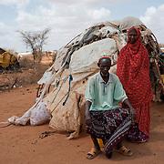 """Kenya, camp de réfugiés de Dadaab. Issek Abdi, 60 ans, Bardere et Nouria, 30 ans, sa femme."""" Au moment où je vous parle, je suis affamé, je n'ai rien à manger"""", Issek dépend entièrement de la nourriture distribuée deux fois dans le mois par les ONG de Dadaab. Cet homme est aveugle, il ne peut travailler pour subvenir aux besoins du couple. Il n'a pas non plus d'enfants pour l'aider. Issek et sa femme Nouria sont arrivés il y a six mois dans les camps du Kenya, contraints de franchir la frontière depuis que les combattants empêchent les ONG de secourir les populations somaliennes en danger.""""Nous avons dû fuir"""". Quatre jours de bus. Ils sont venus tous les deux. Ils n'ont pas encore de carte de rationnement. «On meurt ici, je préfèrerais retourner chez moi»."""