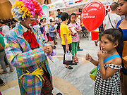 10 JANUARY 2015 - BANGKOK, THAILAND: A girl with a clown during Children's Day festivities in Bangkok. National Children's Day falls on the second Saturday of the year. Thai government agencies sponsor child friendly events and the military usually opens army bases to children, who come to play on tanks and artillery pieces. This year Thai Prime Minister General Prayuth Chan-ocha, hosted several events at Government House, the Prime Minister's office.    PHOTO BY JACK KURTZ