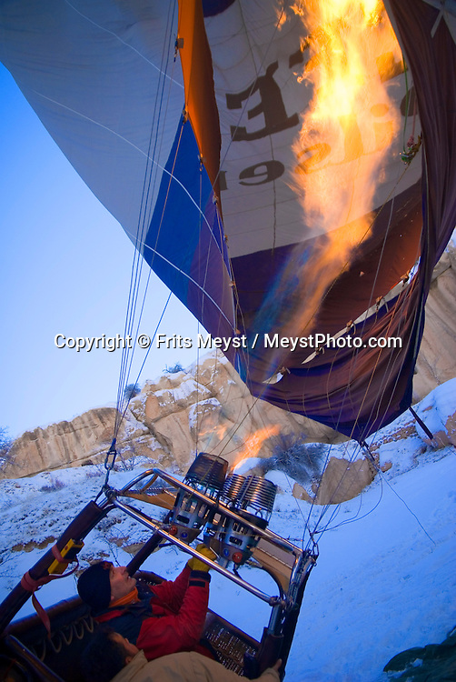 Goreme, Nevsehir, Cappadocia, Turkey. Mike, pilot of Kapadokya Balloons, lights the gas burners for take-off. A fresh pack of snow has turned the winter landscape of Goreme National Park into an even bigger fairy tale. Photo by Frits Meyst/Adventure4ever.com