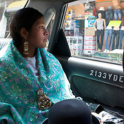 Cholita Yolanda La Amorosa riding in a taxi during media committments in La Paz, Bolivia. Yolanda is a member of the. 'Titans of the Ring' wrestling group who perform on Sunday at El Alto's Multifunctional Centre. Bolivia. The wrestling group includes the fighting Cholitas, a group of Indigenous Female Lucha Libra wrestlers who fight the men as well as each other for just a few dollars appearance money. La Paz, Bolivia, 17th March 2010. Photo Tim Clayton