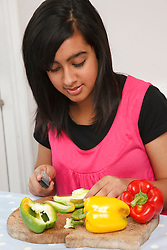 Teenage girl cutting peppers