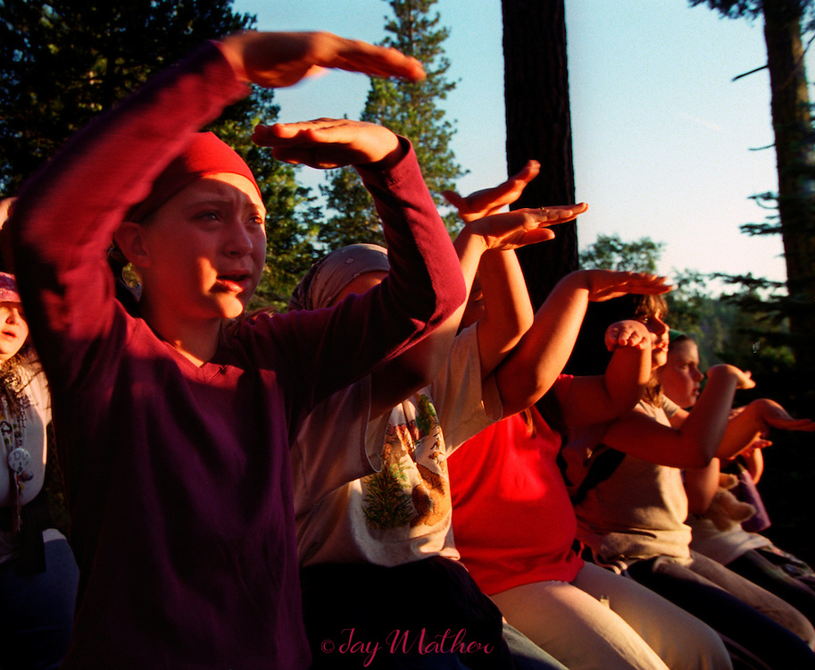 "Girl Scouts, bathed in the lingering glow of sunset, use sign language while they sing a campfire song at Camp Menzies.  The song, ""Moon on the Meadow,"" reflects upon a time when Native Americans were the original inhabitants of the land whre the camp now exists. The group let ro right: Erin Nash (cq), 10, from San Jose; Kassi Branscom (cq), 10, from Modesto; Alex Norris (cq), 9, from San Jose; Samantha Baxter, 10, from Carmichael.  June 27, 2000."