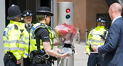 London, June 4th 2017. A man hands a police officer flowers during a massive policing operation in the aftermath of the terror attack on London Bridge and Borough Market on the night of June 3rd which left seven people dead and dozens injured