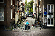 A woman cycles along the Singel Canal in Amsterdam, Netherlands.