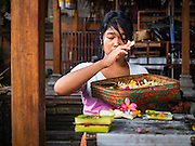 11 OCTOBER 2016 - UBUD, BALI, INDONESIA: A woman prays at the Hindu temple in the market in Ubud. The temple in the market is very busy during the midmorning hours, when market vendors come to pray. The morning market in Ubud is for produce and meat and serves local people from about 4:30 AM until about 7:30 AM. As the morning progresses the local vendors pack up and leave and vendors selling tourist curios move in. By about 8:30 AM the market is mostly a tourist market selling curios to tourists. Ubud is Bali's art and cultural center.      PHOTO BY JACK KURTZ