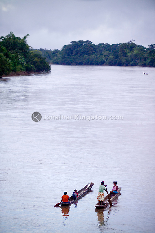 Women navigate the river in two traditional Miskito dugout canoes, using wooden paddles and punts on the Rio Coco, Nicaragua. The Rio Coco starts in the mountains near Somoto and feeds into the Caribbean Ocean. For indigenous Miskito and Mayagna residents, the river acts only as a hypothetical border dividing Honduras and Nicaragua, as many have family members on both sides of the river. On big journeys, people may travel in this type of boat for more than a week before reaching their destination.