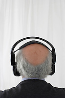 Senior man wearing head phones in studio head and shoulders back view