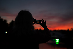 Image ©Licensed to i-Images Picture Agency. 17/07/2014. Henham Park, Suffolk, United Kingdom. A woman takes a photo of a boiling orange sunset  as the hottest day of the year so far draws to an end during the Latitude Festival of music and arts . Picture by Joel Goodman / i-Images