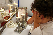 Young Jewish girl of five lights the traditional Shabbat (Sabbath) candles on Friday night