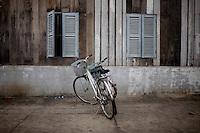 Two bicycles in front of an old building at Tuol Sleng, Pol Pot's prison during the Khmer Rouge in the late 1970s, where over a million people were killed, in Phnom Penh, Cambodia.