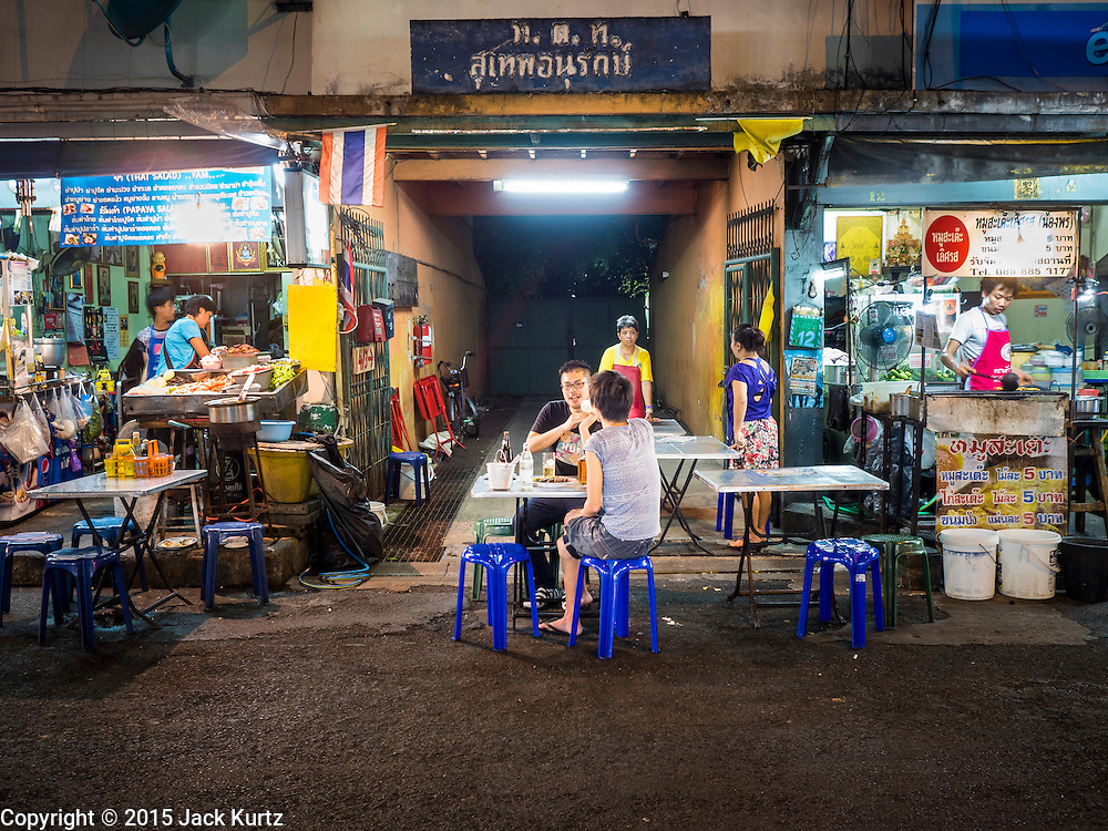 26 MAY 2015 - BANGKOK, THAILAND: People eat at street food stalls on Sukhumvit Soi 38 in Bangkok, one of the most famous street food locations in the Thai capital. The food carts and small restaurants along the street have been popular with tourists and Thais alike for more than 40 years. The family that owns the land along the soi recently decided to sell to a condominium developer and not renew the restaurant owners' leases. More than 40 restaurants and food carts will have to close. The first wave of closings could start as soon June 21 and all of the restaurants are supposed to close over the next several months.     PHOTO BY JACK KURTZ