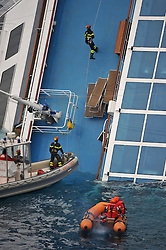 "Rescue workers and divers on The Wrecked Cruise Ship ""Costa Concordia"" in Giglio, Italy, as the ship starts to move. Photo By Nick Cornish/ I-Images."