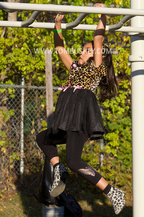 Middletown, New York  - A girl wearing a costume climbs on playground equipment during the Halloween Fall Festival at the Middletown YMCA's Center for Youth Programs on Oct. 25, 2014.