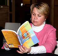 Tina Ortiz of Mark Fornes Realty checks out keynote speaker Marty Grunder's book during the Dayton Development Coalition annual meeting in the Schuster Center in downtown Dayton, Wednesday, January 11, 2012.