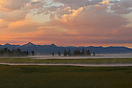 Colored by smoke, the sun rises over the Absaroka Mountains and Pelican Creek in Yellowstone National Park's Lake Area.
