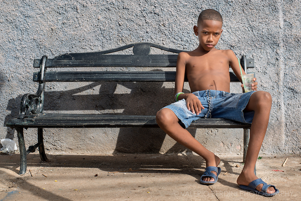 A child take a rest from playing having a fresh lemon slush on a bench in Remdios, Cuba.