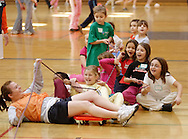Middletown, N.Y. - A group of 7-year-old girls react as one of their leaders fall over during a game at National Women in Sports Day on Feb. 11, 2006. Orange County Community College's Department of Movement Science celebrated the 20th Anniversary of National Girls and Women in Sports Day by holding an event for young girls that included volleyball, basketball, soccer, games and swimming. ©Tom Bushey