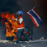 A Thai anti-government protester with Thai's flag walks near a burning tyre in central Bangkok, Thailand, 14 May 2010. Thai Prime Minister Abhisit Vejjajiva launched a crackdown on a Bangkok protest after officially scrapping an offer to hold an early election this year in a bid to placate the anti-government demonstrators in which the protestors' chief military security adviser, Major General Khattiya Sawasdipol, better known by his nickname Seh Daeng, was shot in the head 13 May. Roadblocks by military and protesters have been set up around the Ratchapradong occupied zone causing traffic chaos and tense standoffs and exchange of gunfire between soldiers and protesters. EPA/AHMAD YUSNI