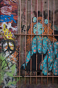 Depiction of a caged woman made as sprayed graffiti on an east London Victorian brick wall.