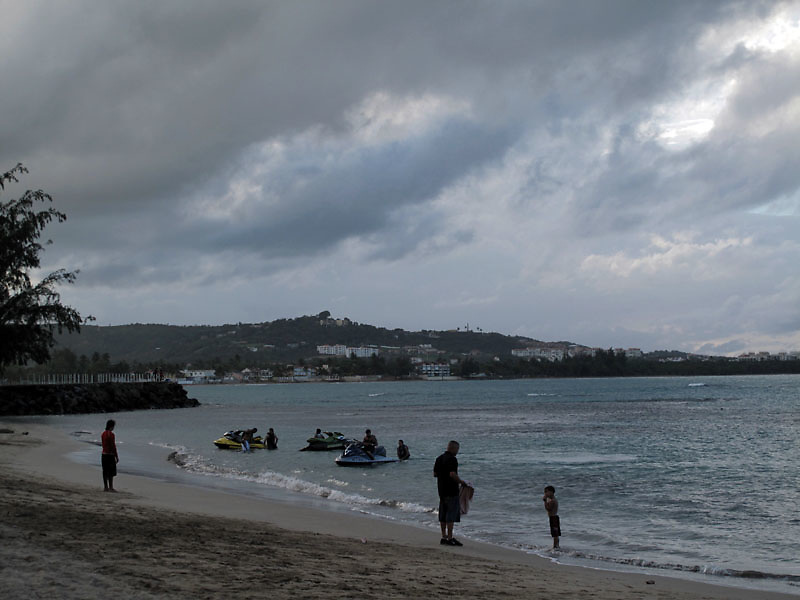 Beachgoers in the shallow water of the Balneario de Luquillo or Luquillo Beach at dusk in Puerto Rico..Photo by Angel Valentin, copyright 2009.