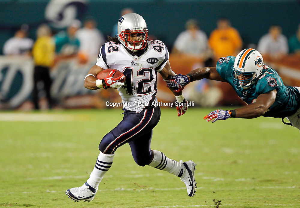 New England Patriots running back BenJarvus Green-Ellis (42) runs the ball while avoiding a diving tackle attempt by Miami Dolphins linebacker Cameron Wake (91) during the NFL week 1 football game against the Miami Dolphins on Monday, September 12, 2011 in Miami Gardens, Florida. The Patriots won the game 38-24. ©Paul Anthony Spinelli