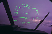 We look through the windscreen of a Royal Air Force C-130-J Hercules to see a pilots-eye view of his fixed head-up-display (HUD), while in flight over Hampshire during the Farnborough Air Show. We see the aircraft flying data in green set against the magenta colour (color) of the clouds and sky beyond. The pilot will see the statistics that are important aspects of his aeroplane's altitude, compass heading, localiser, air speed, pitch, roll and yaw. Head-up displays are increasingly important to military and commercial aircraft (airplanes) when information can be displayed without obstructing the user's front view front. The second type of HUD is mounted within a protective helmet visor. The C-130 Hercules primarily performs the tactical portion of airlift operations. The aircraft is capable of operating from rough, dirt strips and is the prime transport for air dropping troops and equipment into hostile areas. The C-130-J is the newer generation digital version with fully integrated digital avionics; color multifunctional liquid crystal displays including the HUD; state-of-the-art navigation systems with dual inertial navigation system and global positioning system; fully integrated defensive systems; low-power color radar; digital moving map display; new turboprop engines with six-bladed, all-composite propellers; digital auto pilot; improved fuel, environmental and ice-protection systems; and an enhanced cargo-handling system..