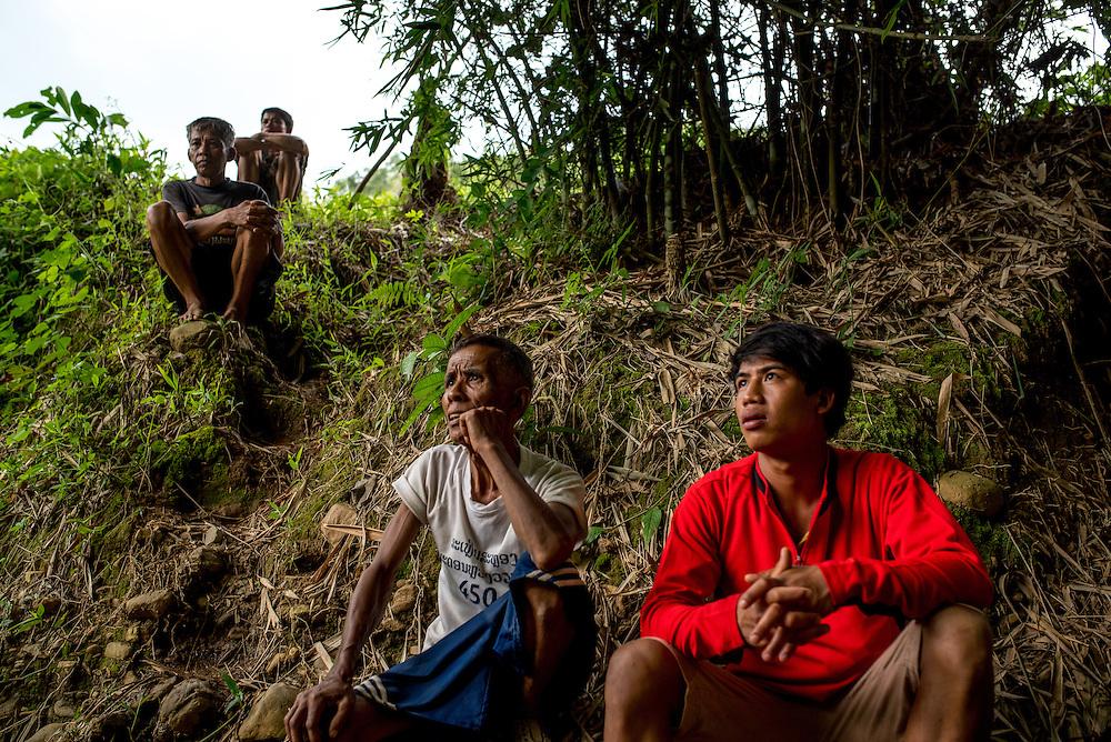 Men gather near a small water turbine in the village of Khoc Kham.