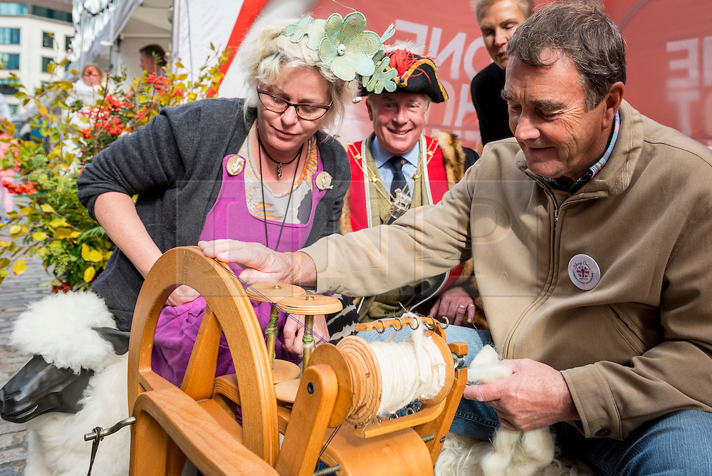 © Licensed to London News Pictures. 25/09/2016. London, UK. Former Formula One driver, Nigel Mansell, practices spinning wool in a wool market, taking place alongside the annual Sheep Drive organised by the Worshipful Company of Woolmen taking place across London Bridge.  The event raises funds for the Lord Mayor's Appeal and the Woolmen's Charitable Trust. Photo credit : Stephen Chung/LNP