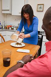 Elderly black man with white woman carer preparing his dinner