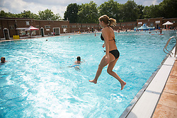 © licensed to London News Pictures. London, UK 26/08/2013. People enjoying the hot weather on bank holiday on Monday, 26 August, 2013 at Parliament Hill Lido swimming pool in London. Photo credit: Tolga Akmen/LNP