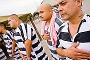 "17 JULY 2006 - PHOENIX, AZ: Inmates WILLIE ZAMORA (RIGHT), ARTHUR HERNANDEZ and others stand with their hands over the hearts while the National Anthem is played in ""Tent City"" in the Maricopa County Jail in Phoenix, AZ. There are about 650 inmates living in the tents. Maricopa County Sheriff Joe Arpaio recently started playing the Star Spangled Banner and God Bless America twice a day in the county jails. Inmates are encouraged, but not forced, to stand at attention with their hands over their hearts, when the music is played. When asked about the new policy Arpaio said, ""Our men and women are fighting and dying for our country in Iraq and that's the least these inmates can do."" In 2011, the US Department of Justice issued a report highly critical of the Maricopa County Sheriff's Department and the jails. The DOJ said the Sheriff's Dept. engages in widespread discrimination against Latinos during traffic stops and immigration enforcement, violates the rights of Spanish speaking prisoners in the jails and retaliates against the Sheriff's political opponents.      PHOTO BY JACK KURTZ"