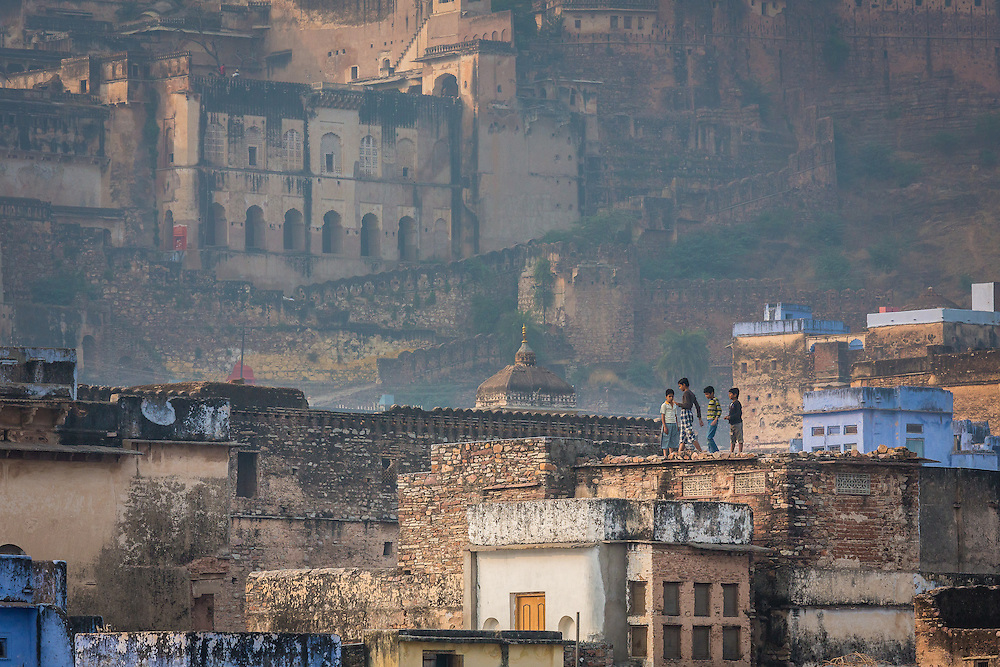 Four kids play in the maze of rooftops in the old part of the city of Bundi, with the palace in the background.
