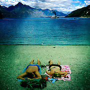 Sunbathers on the beach at Queenstown as the TSS Earnslaw, the 100 year old vintage coal fired passenger steam ship sails on Lake Wakatipu, Queenstown, New Zealand. The popular tourist attraction is celebrating it's centenary year with celebrations planned for October 2012.  Queenstown, Central Otago, New Zealand. 29th February 2012. Photo Tim Clayton