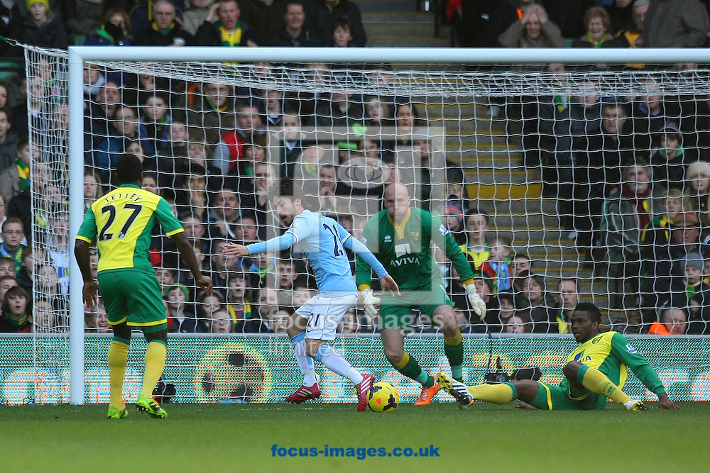 Picture by Paul Chesterton/Focus Images Ltd +44 7904 640267<br /> 08/02/2014<br /> Joseph Yobo of Norwich and Alexander Tettey of Norwich combine to deny David Silva of Man City during the Barclays Premier League match at Carrow Road, Norwich