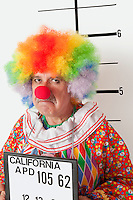 Portrait of angry senior clown during mug shot