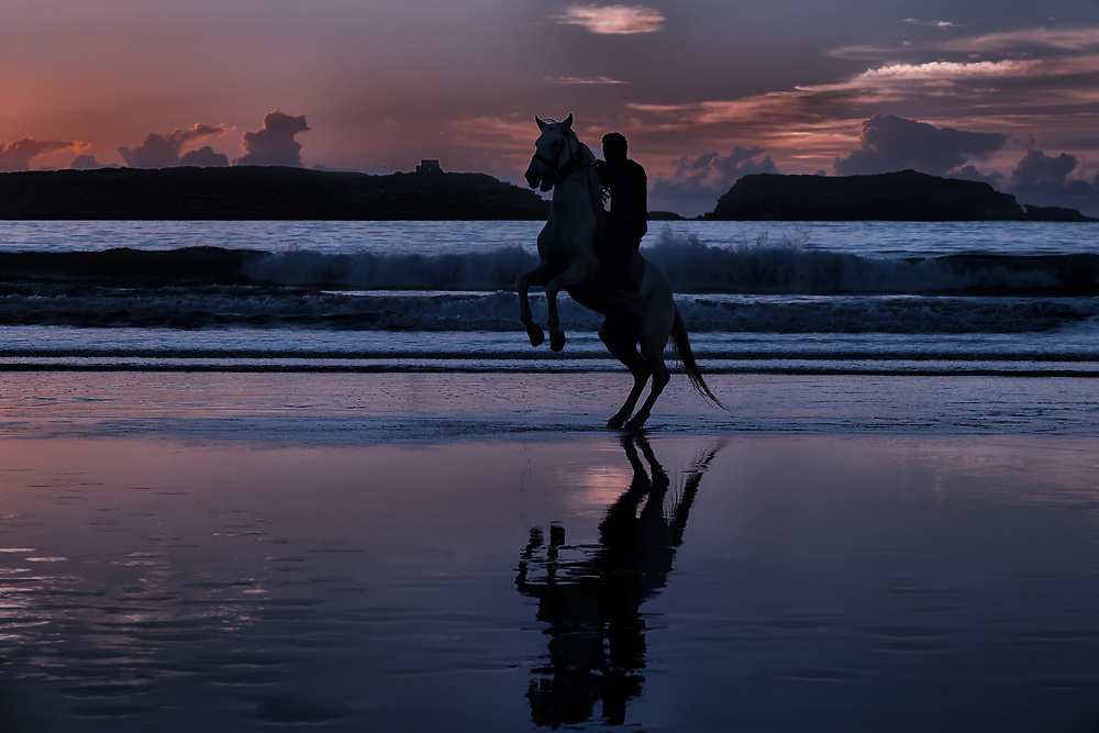 Horse rider at the beach at dusk.