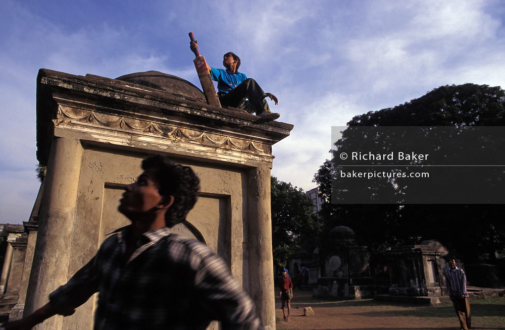 """Young men watch a ball fly over their heads into the distance during a spontaneous game of cricket routinely held (in the 1990s) among the tombs and mausolea of dead British Raj officials and family members, buried in Victorian-era Park Street cemetery, on 18th November 1996, in Kolkata, India. The Park Street cemetery was amed """"Park Street"""" after the private deer park built by Sir Elijah Impey around Vansittart's garden house. The cemetery (opened in 1767) served as a burial ground for the European expatriates who were settled in Calcutta during the colonial period. The cemetery was closed in 1840 due to lack of burial space and is now a heritage site, preserved by the Archaeological Survey of India (ASI)"""