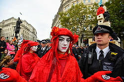 © Licensed to London News Pictures. 10/10/2019. LONDON, UK. Members of the Red Brigade, supporters of Extinction Rebellion, march silently around police who have surrounded a wooden structure, which contains activists secured to it, in Trafalgar Square during day 4 of Extinction Rebellion's climate change protest in the capital.  Activists are calling on the Government to take immediate action against the negative impact of climate change.  Photo credit: Stephen Chung/LNP