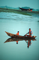 Near Barisal in the Bay of Bengal father and son canoe through a tidal canal. The region is interlaced with canals and streams. This river delta system is always in danger of flooding. Millions of people live in poverty and in fear of losing everything in the next flood.