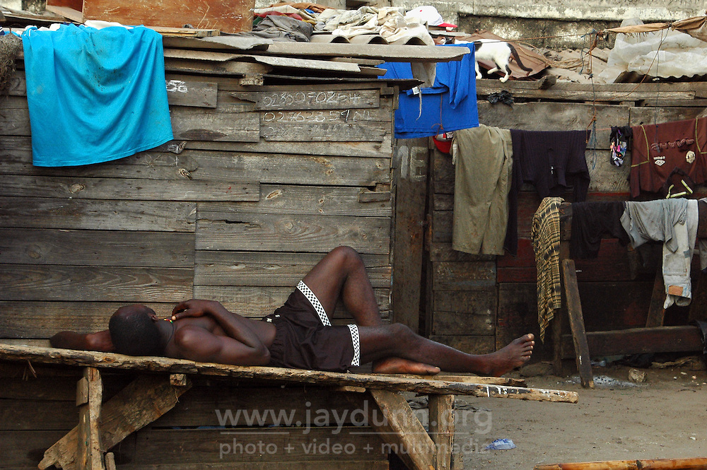 GHANA,Accra,Jamestown, 2007. An exhausted fisherman sleeps by his oceanfront home near Jamestown, one of Accra's oldest communities.