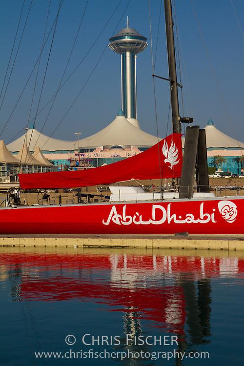 "View of Marina Mall and Marina Mall Tower from Abu Dhabi Marina & Yacht Club. Red sailboat named ""Abu Dhabi"" in foreground."