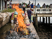 "11 SEPTEMBER 2015 - BANGKOK, THAILAND:  People burn ""ghost money"" before a food distribution for poor members of the community at Wat Kalayanamit in the Thonburi section of Bangkok. Food distribution is a common way of making merit in Chinese Buddhist temples. Wat Kalayanamit, a Thai Theravada temple, was founded by a Chinese-Thai family in the 1820s and observes both Thai and Chinese Buddhist traditions. The food distribution was not related to the temple's efforts to evict people living on the temple grounds, but many of the people at the food distribution live in the houses the temple plans to raze.   PHOTO BY JACK KURTZ"