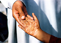 Pakistan, Northwest Frontier Province, 2004. On the hand of a child, wedding henna, and a welcome from Tahkt-e Bhai, a close-knit town outside Peshawar. Behind high walls, the women could be heard celebrating separately.