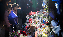 © Licensed to London News Pictures. 28/12/2016. London, UK. Two young girls and their mother look at tributes, left at the door of George Michael's London home in Highgate, North London. Pop superstar George Michael died on Christmas day at his Oxfordshire home on the River Thames aged 53. Photo credit: Ben Cawthra/LNP