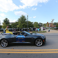 Tupelo High School freshman maid Zipporah Nabors  waves to the crowd as she passes by with other maids during Thursday's Homecoming Parade along West Main Street.