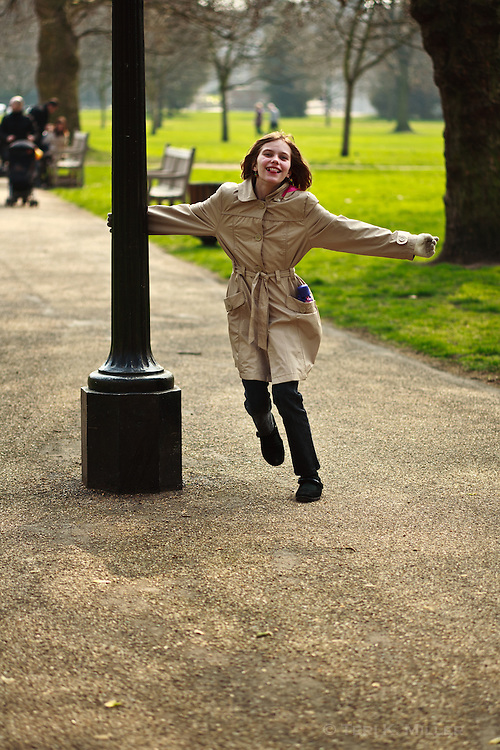 A young girl dances around a light post in Hyde Park, London, England.