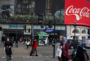 Londoners and visitors to London walk through Piccadilly Circus  where digital advertising is being displays on the large screens above a branch of Barclays Bank and Boots the Chemist, on 6th March 2020, in London, England.