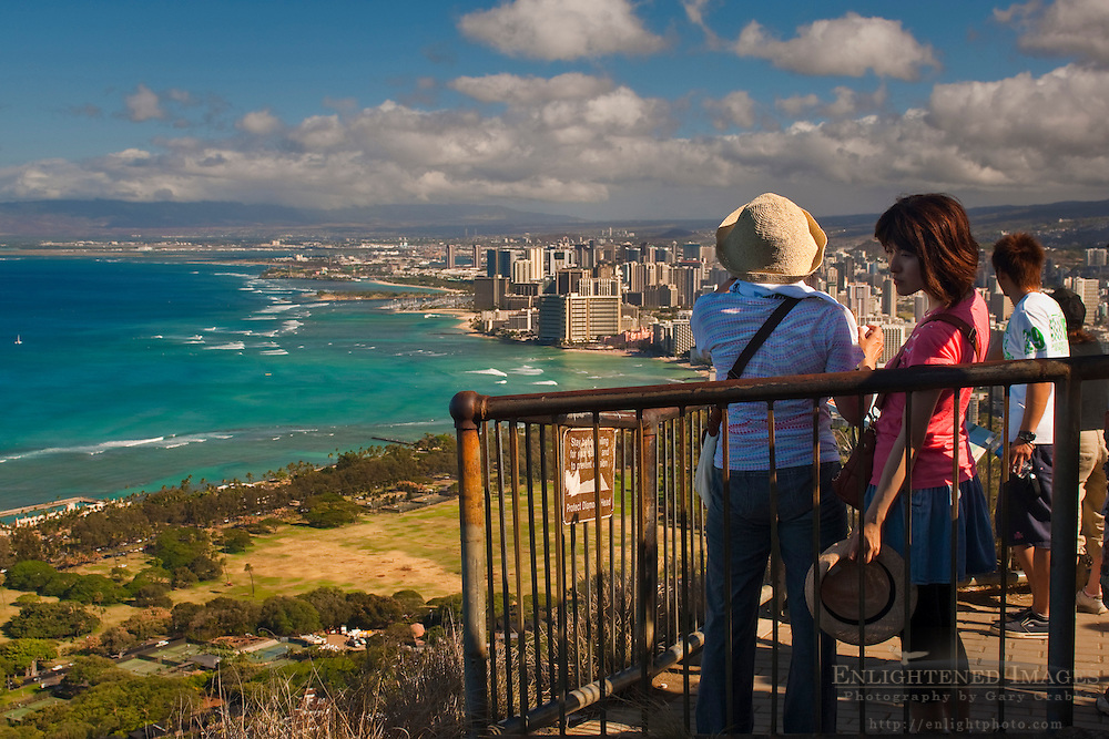 Tourists at the top of Diamond Head Crater Park, looking out toward Honolulu, Oahu, Hawaii