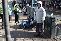 © Licensed to London News Pictures . 24/10/2018. Leeds , UK . A man sits on the pavement against a utility cabinet on Duncan Street as police walk by . At least six people sleeping rough have died in the Metropolitan Borough of the City of Leeds since March 2017 and West Yorkshire Police say they responded to 66 reported cases of people suffering the effects of Spice in July 2018 , a large increase on previous months . Photo credit : Joel Goodman/LNP
